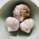 Three heads of whole garlic in a bowl.